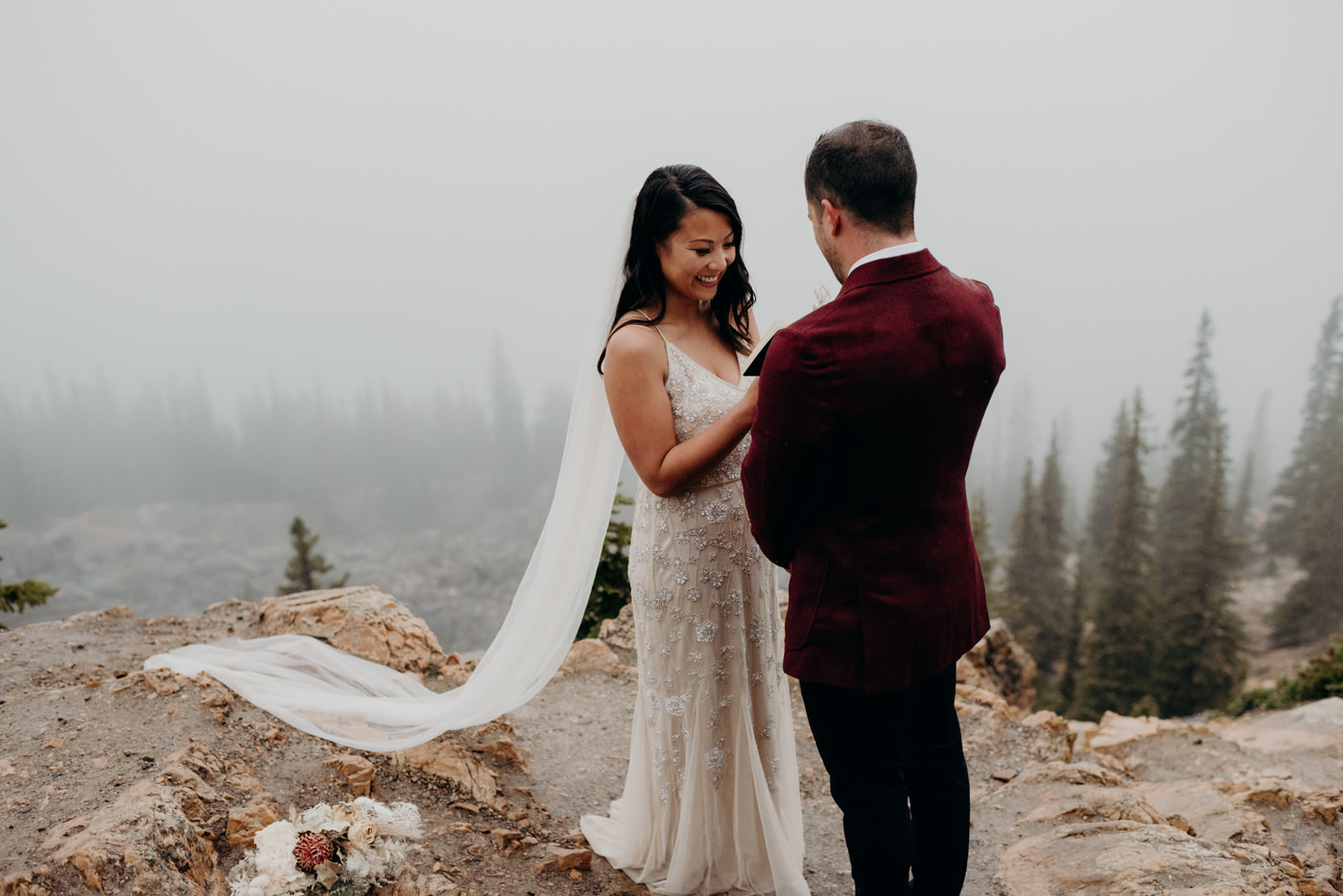 bride smiling and reading vows to groom in the mountains