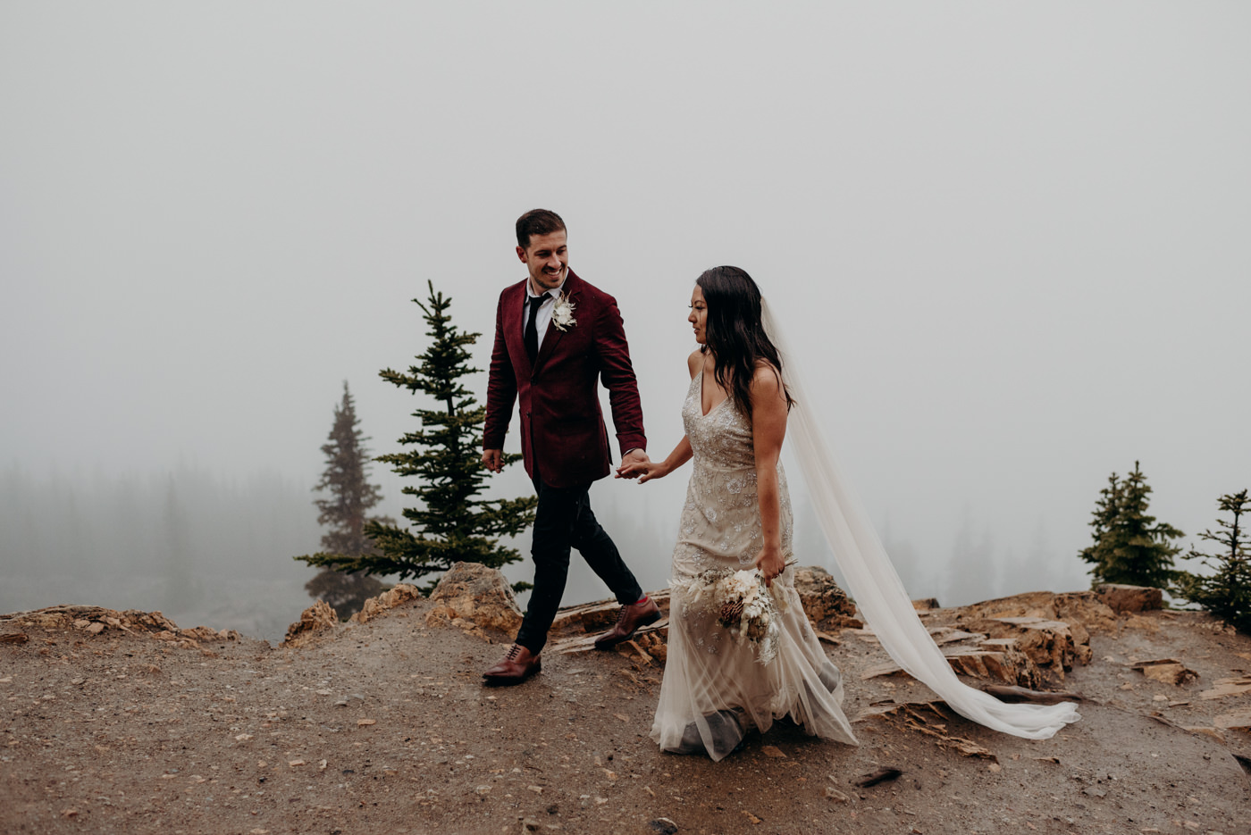 adventurous elopement at Banff National Park, bride and groom walking in the rain