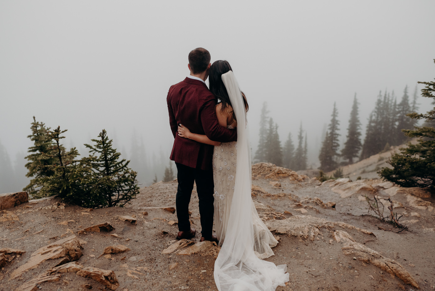 bride and groom hugging and looking off onto misty cloudy tree tops at Peyto Lake