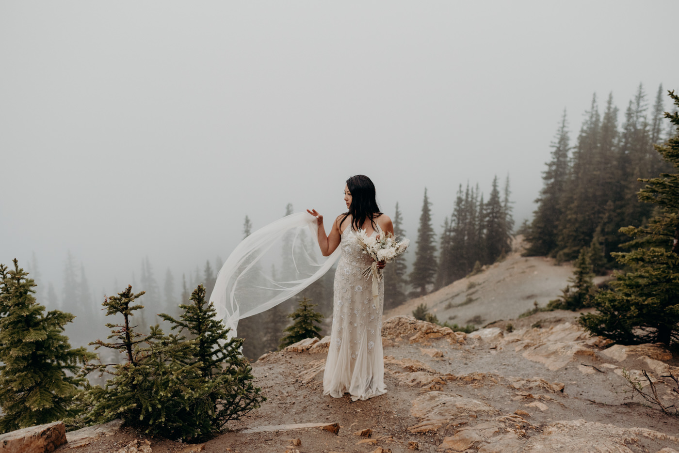 Bride on mountainside on a rainy cloudy morning