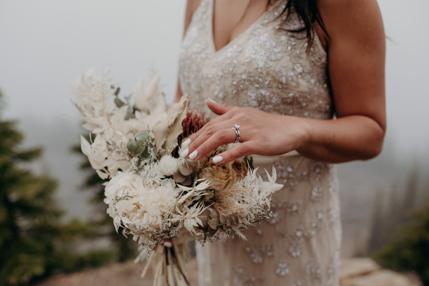 bride touching dried flower bouquet
