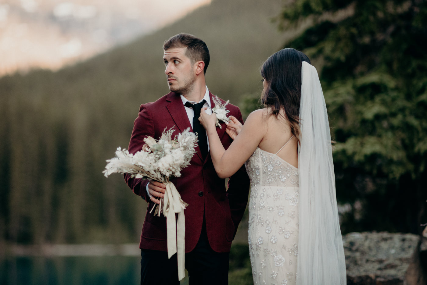 bride adjusting grooms boutonniere, Moraine Lake elopement