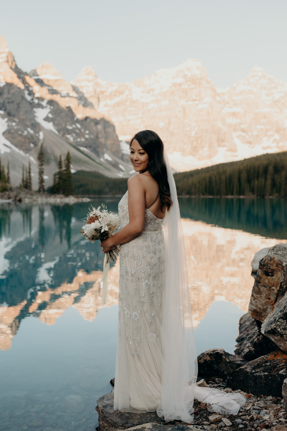 bride standing on rock with mountains in background, Moraine Lake elopement