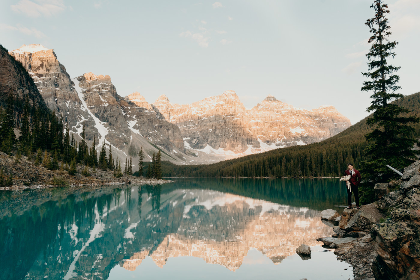 groom holding bouquet at Moraine lake sunrise elopement