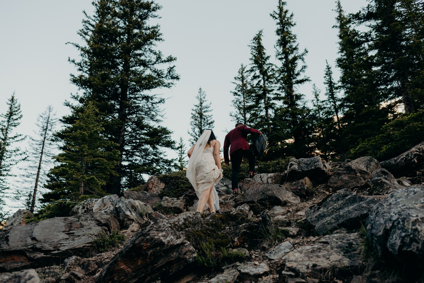 bride and groom climbing rocks on wedding day at Moraine Lake