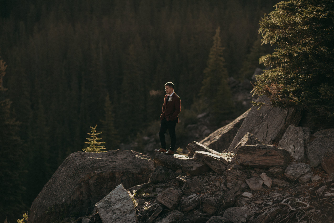 groom standing on rock in morning light, Banff National Park elopement