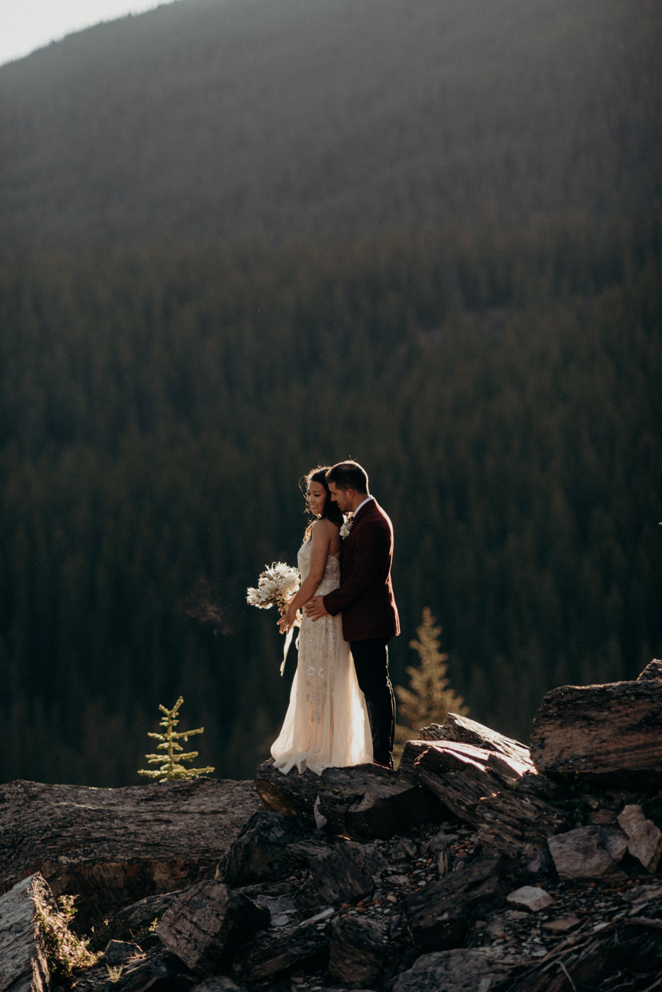 Bride and groom standing in morning light in banff National park