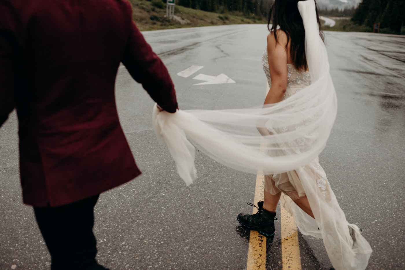 groom holding veil as couple runs across the road