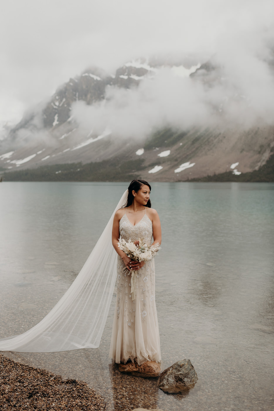 bride standing on rock in water at Bow lake
