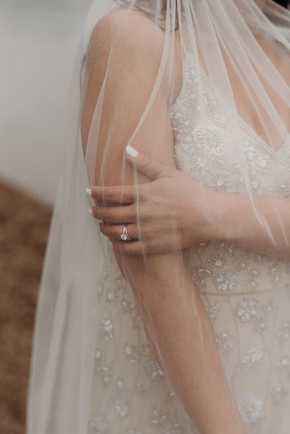brides wedding ring covered in veil