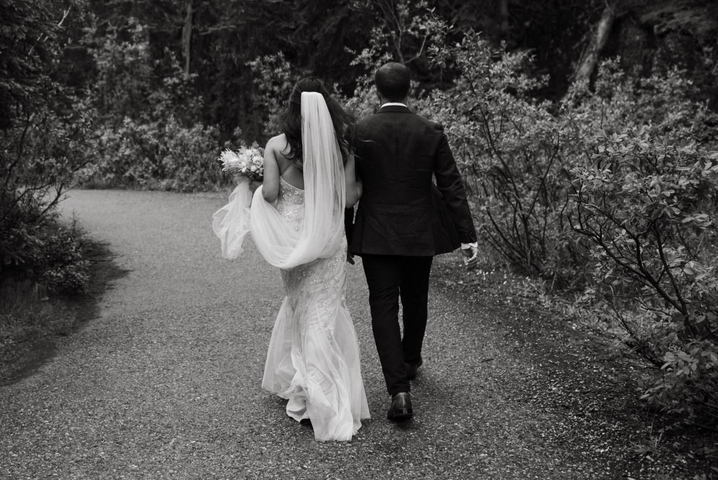 Bride and groom walking on path in mountains