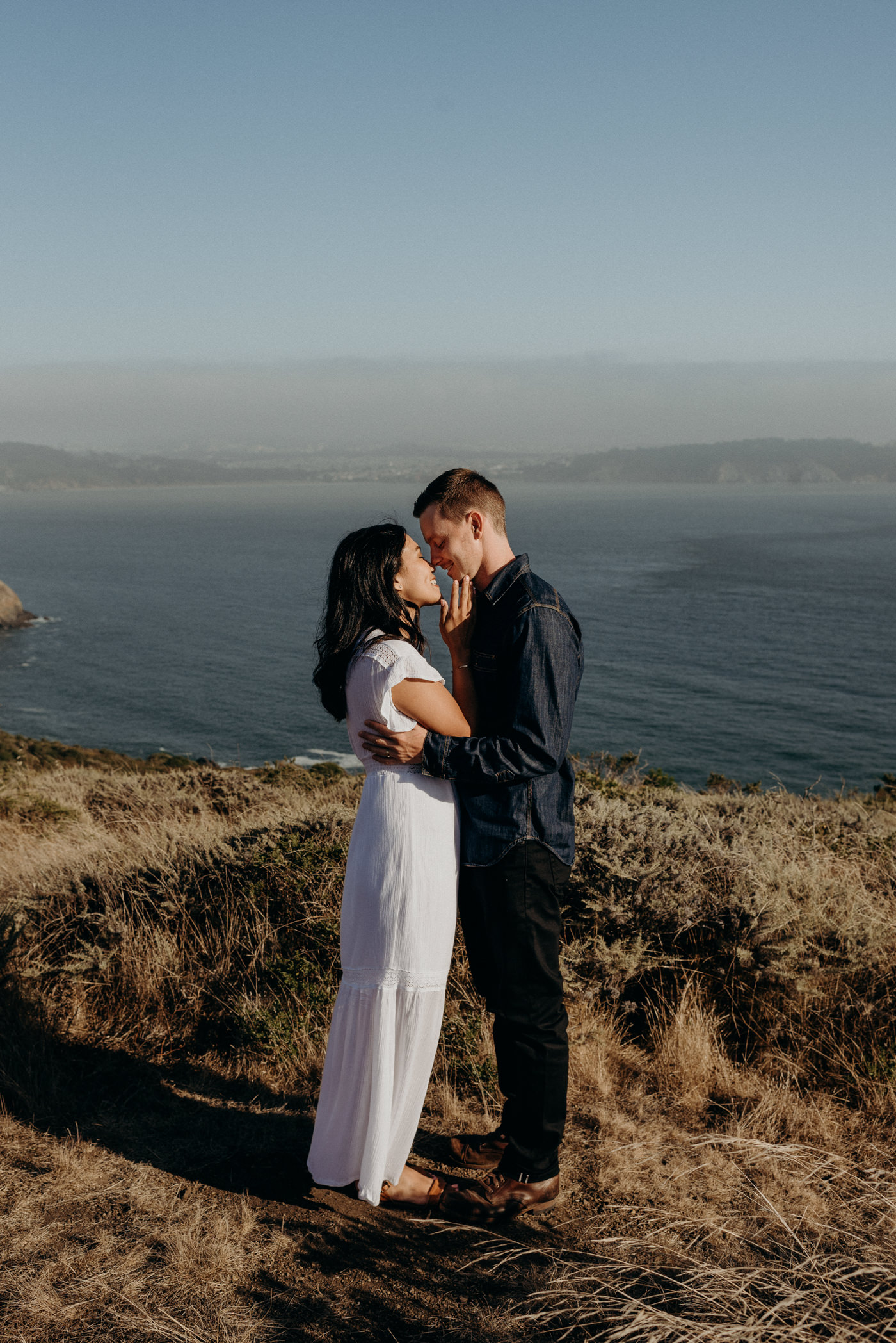 couple hugging and about to kiss while standing on cliff