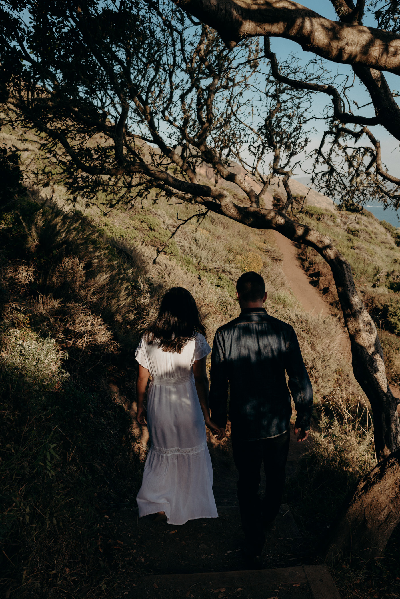 Couple holding hands and walking on trail towards beach at Marin Headlands