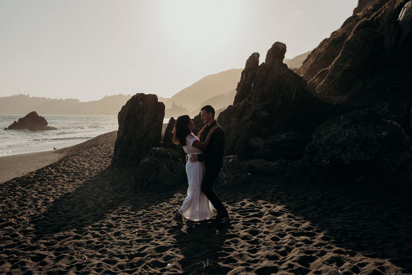 Dancing in the setting sun light on the beach during this Marin Headlands engagement shoot