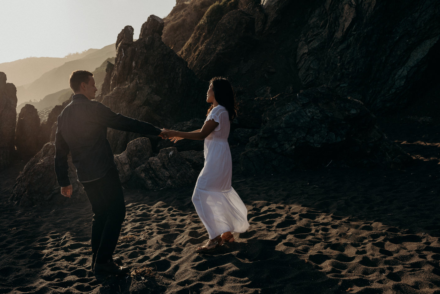 Dancing in the setting sun light on the beach during this Marin Headlands couple shoot