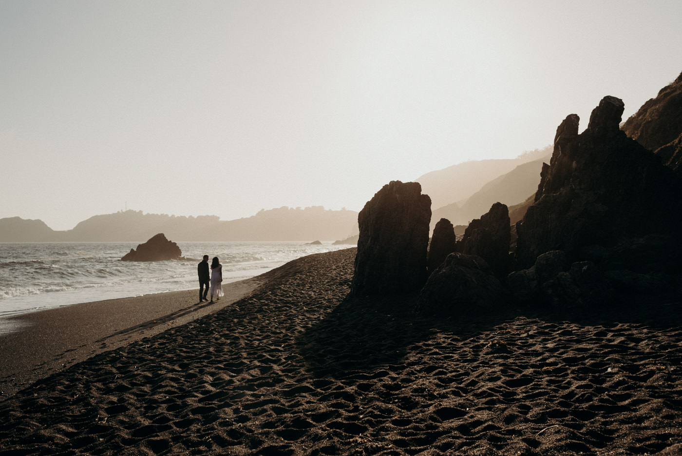 Couple walking on beach at sunset at Marin Headlands