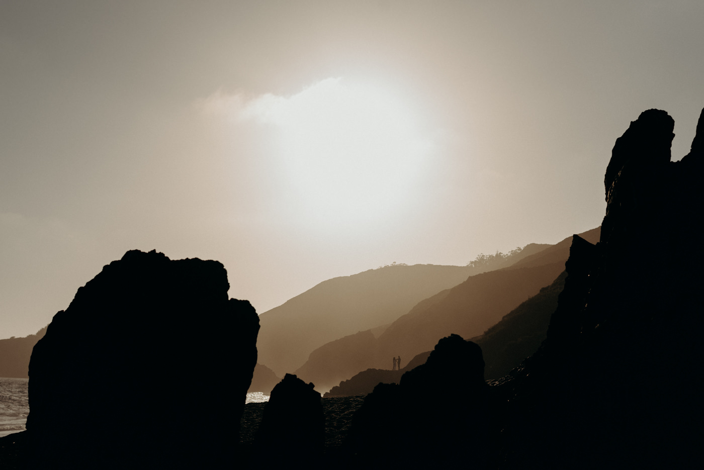 Couple standing on rock in the distance at sunset at Marin Headlands