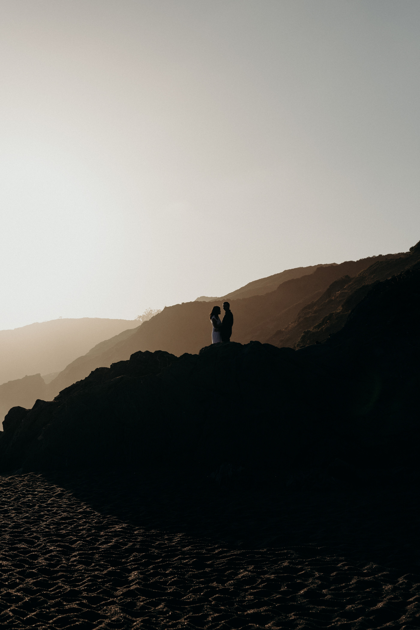 Couple standing on rocks at sunset at Marin Headlands