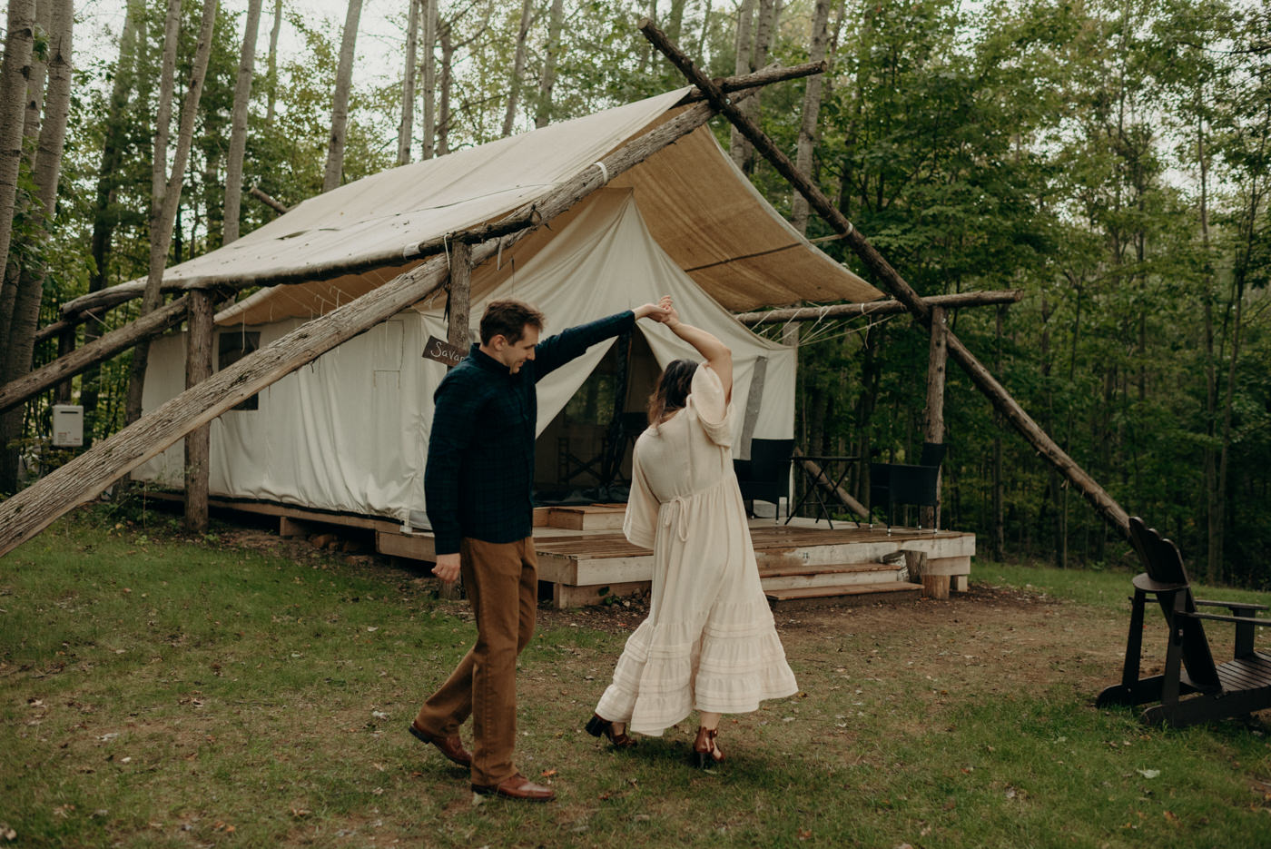 Couple dancing in front of glamping tent