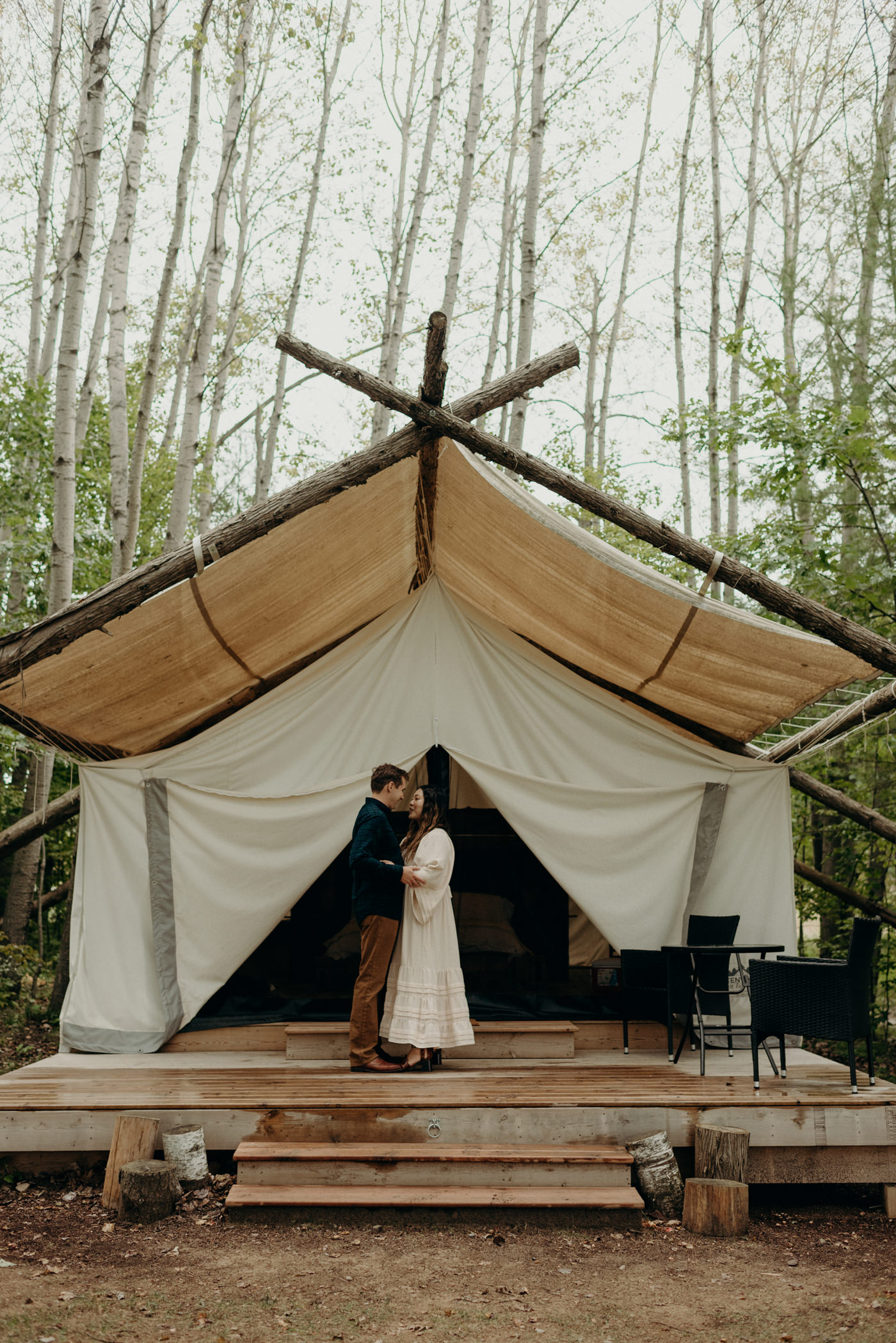 Couple standing on deck of their canvas tent