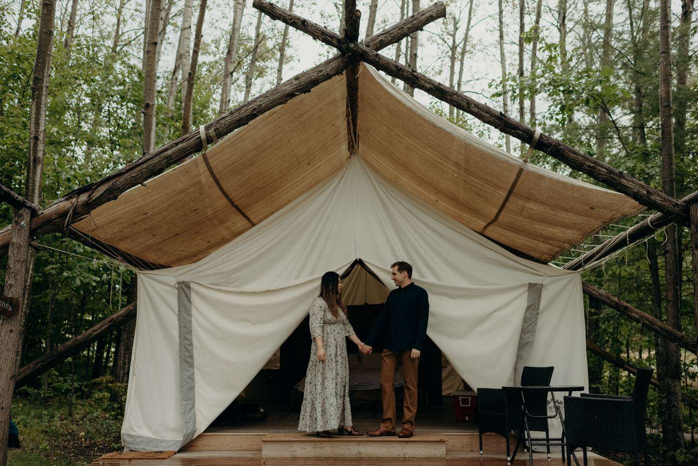Couple standing on front deck of glamping tent