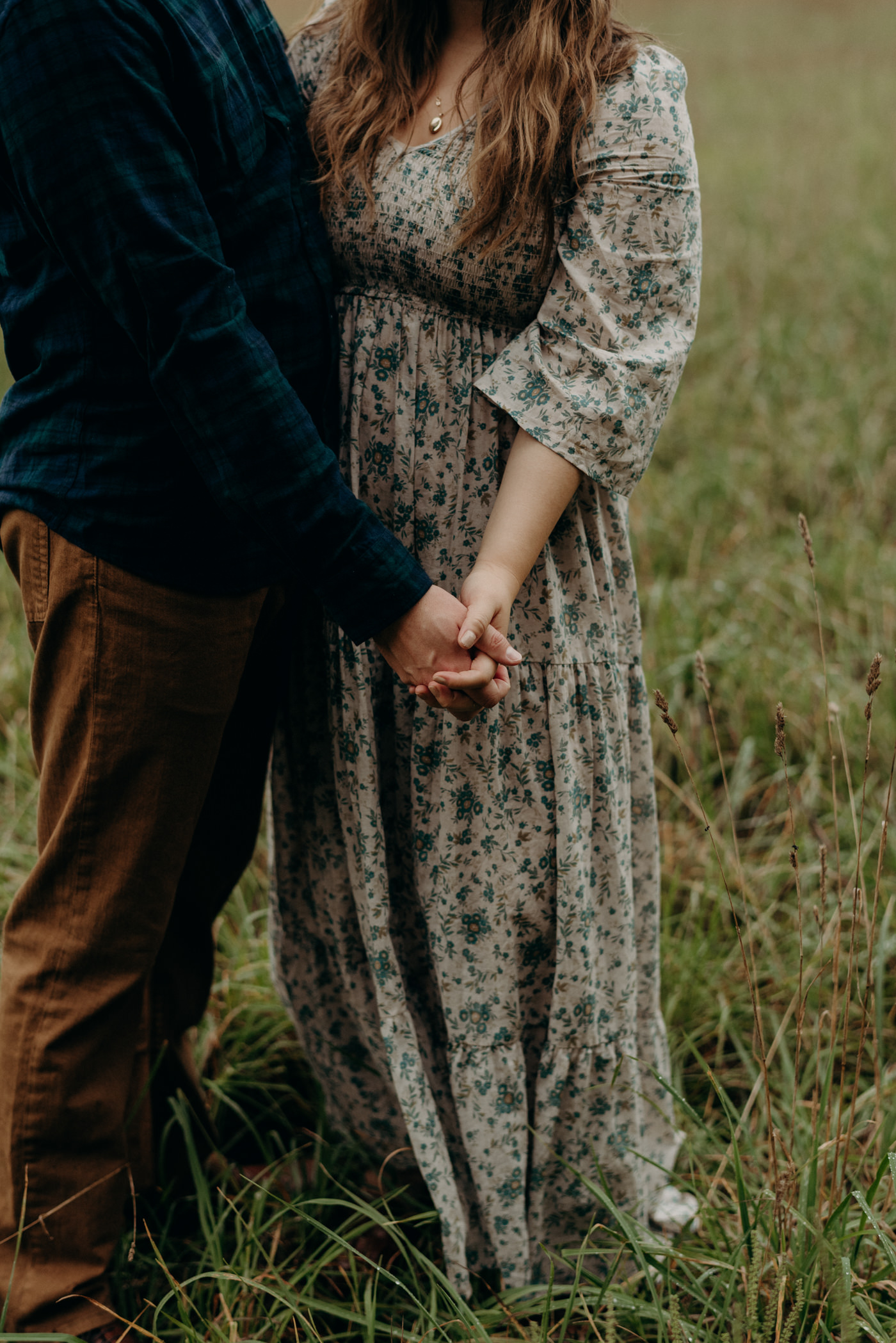 holding hands in a field for engagement shoot