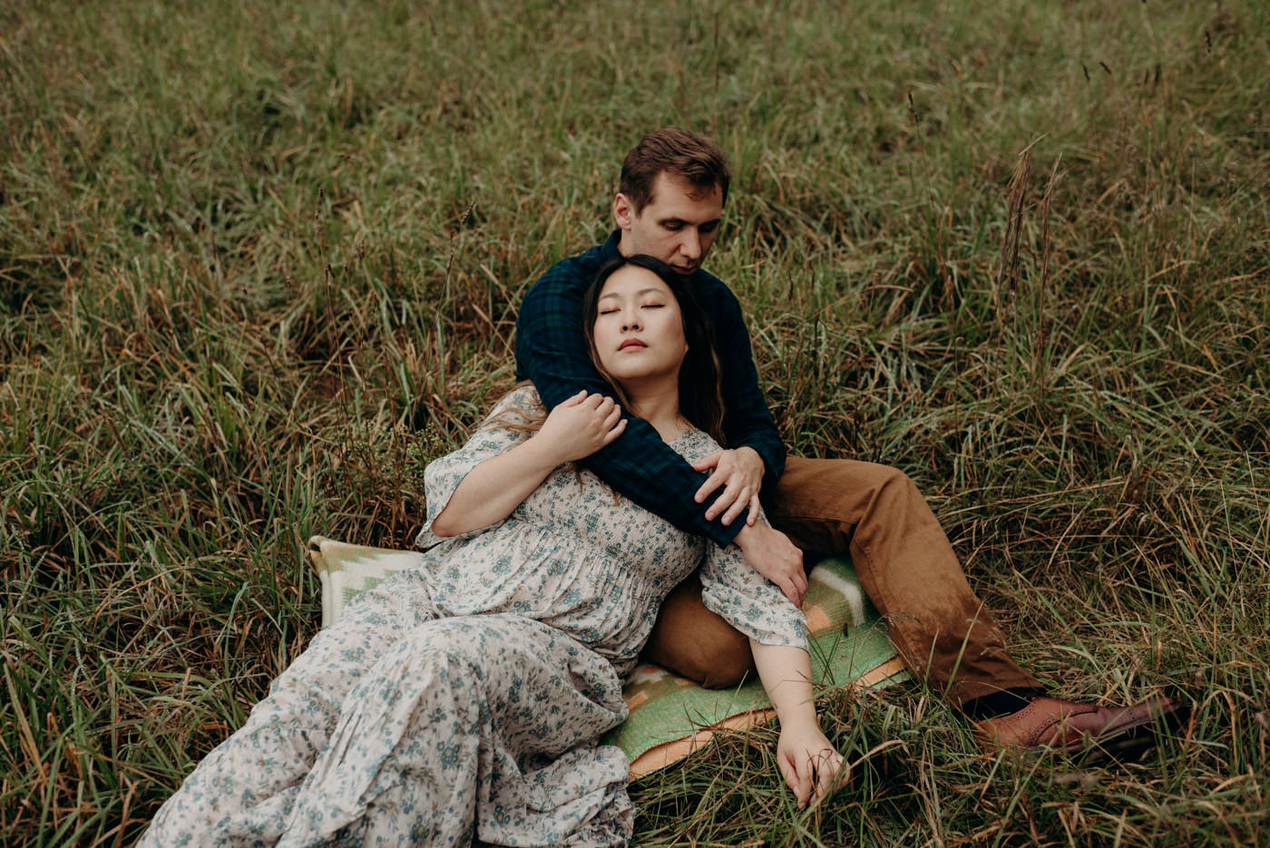 Couple lying in a field during their dreamy Whispering Springs engagement session