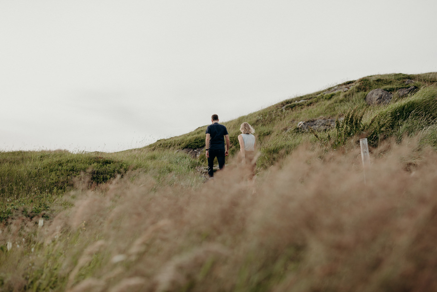 Couple walking in grassy trail to artist residence on Fogo Island