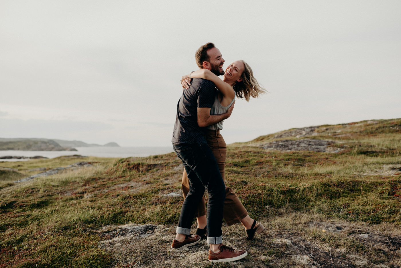 Couple hugging and laughing by the ocean, Fogo island couple shoot