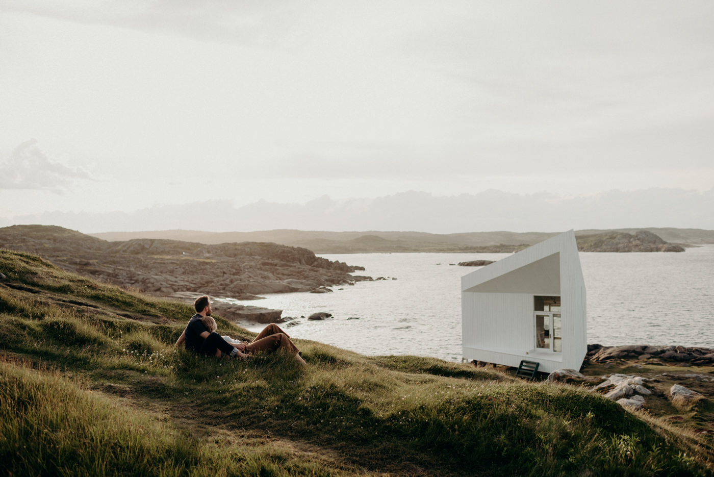Couple shoot at sunset with Squish studio in background at Fogo Island
