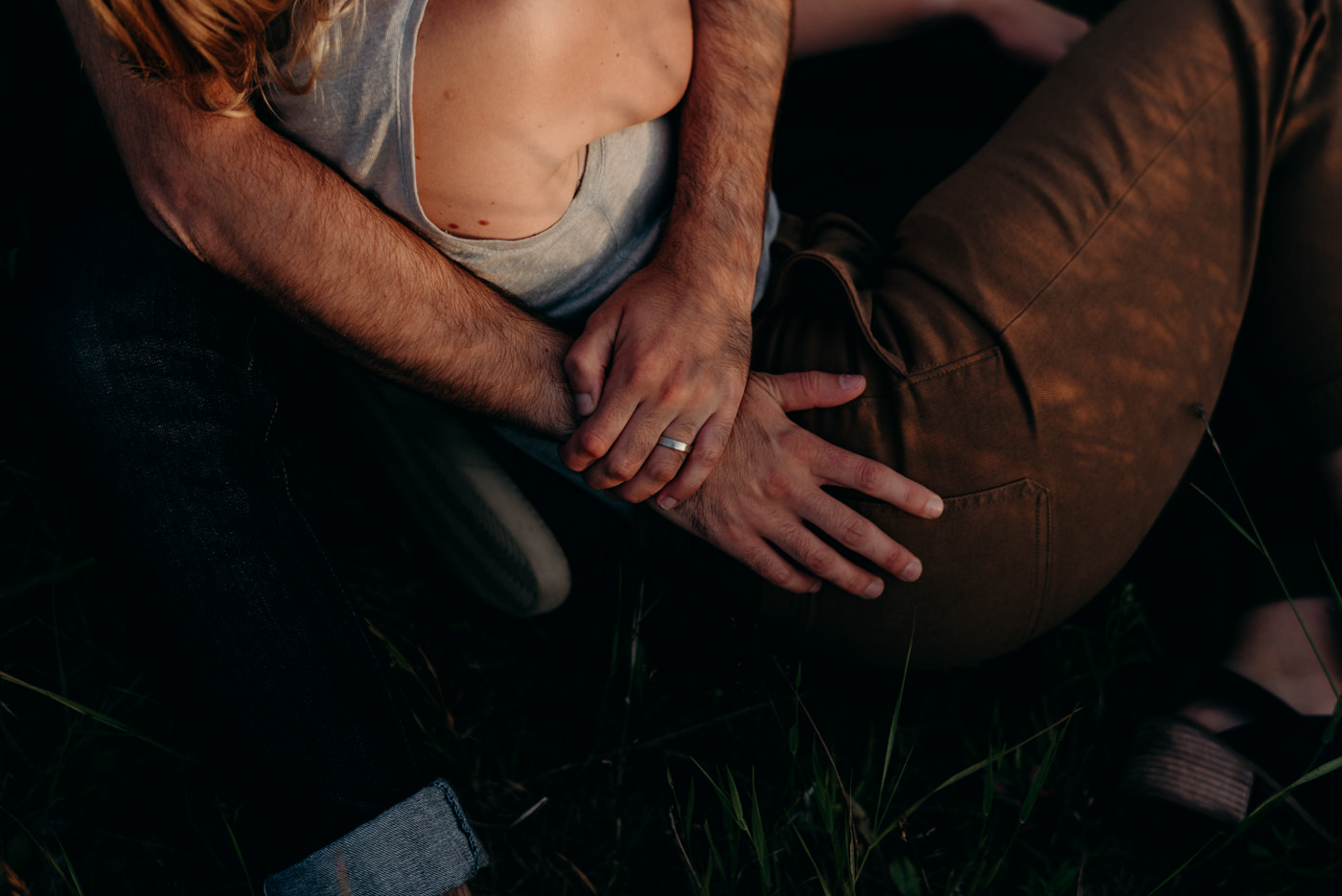 couple sitting in grass at sunset