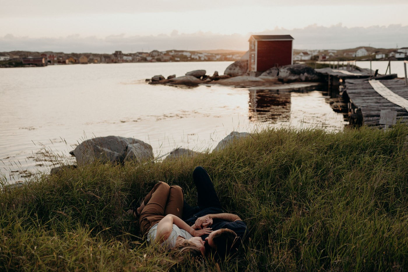 Couple lying in grass at sunset in Tilting, Fogo Island