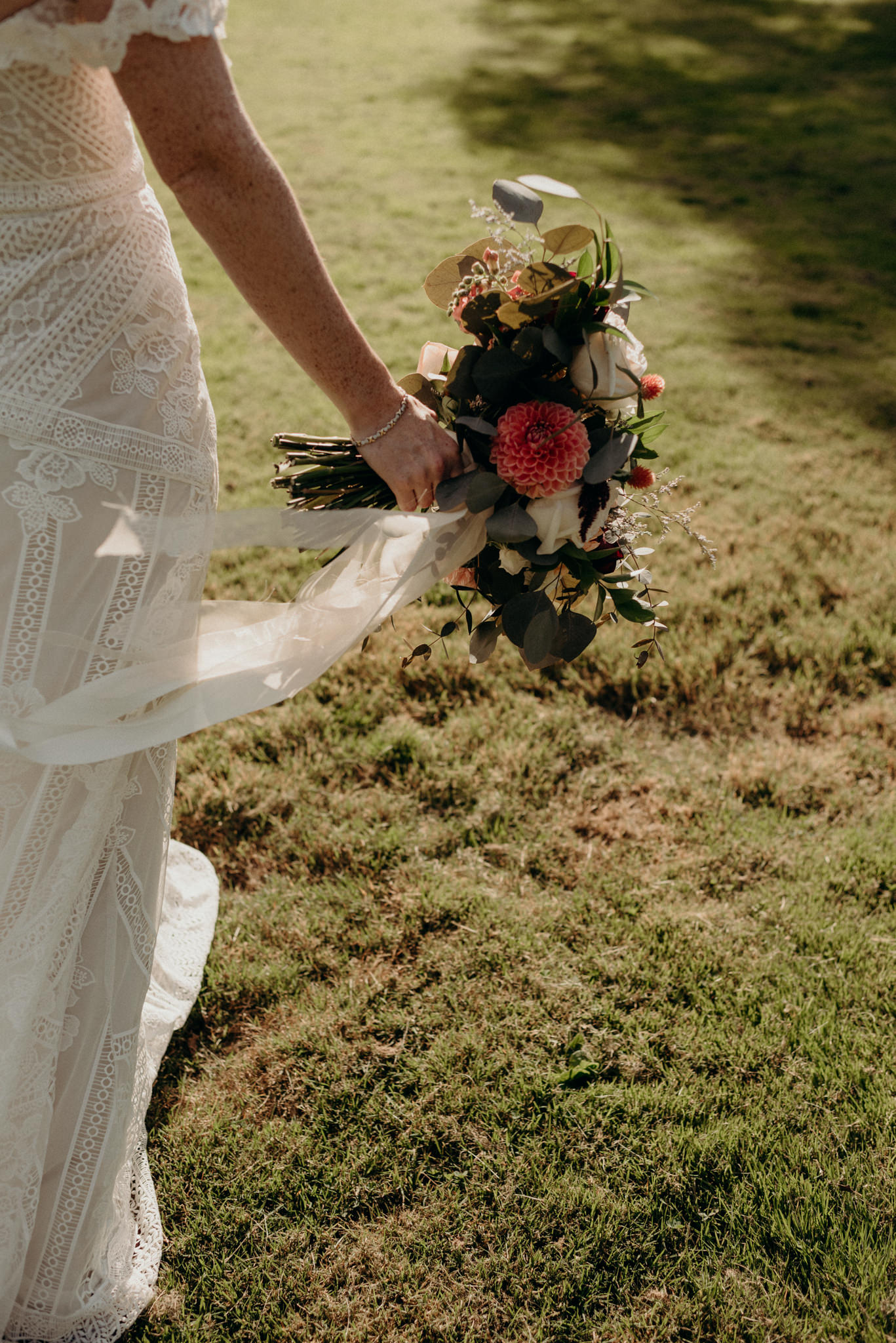 bride walking on grass holding bouquet