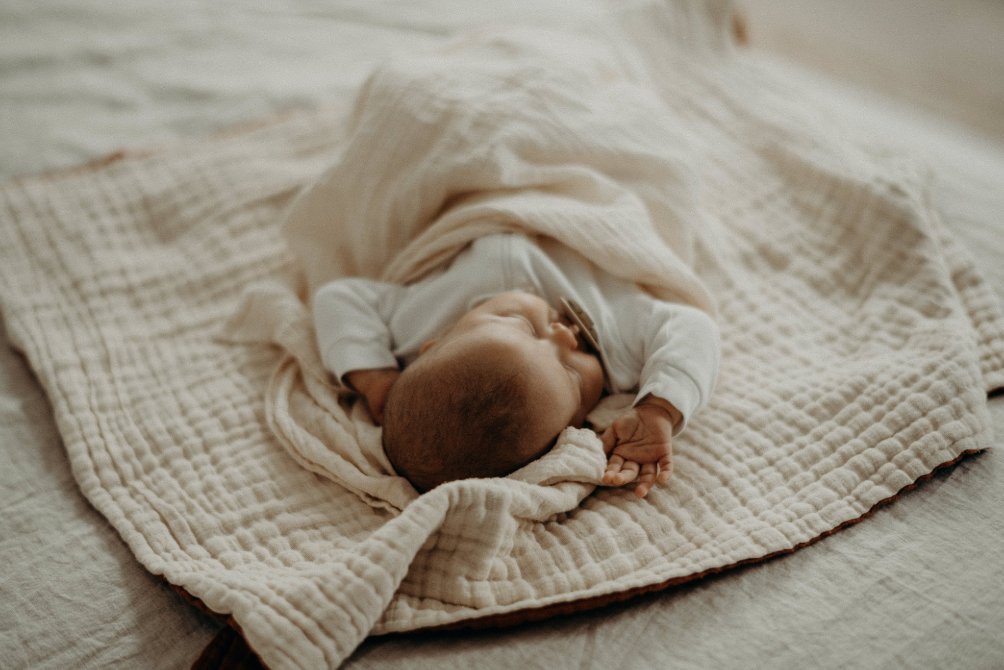 baby sleeping in neutral bedding