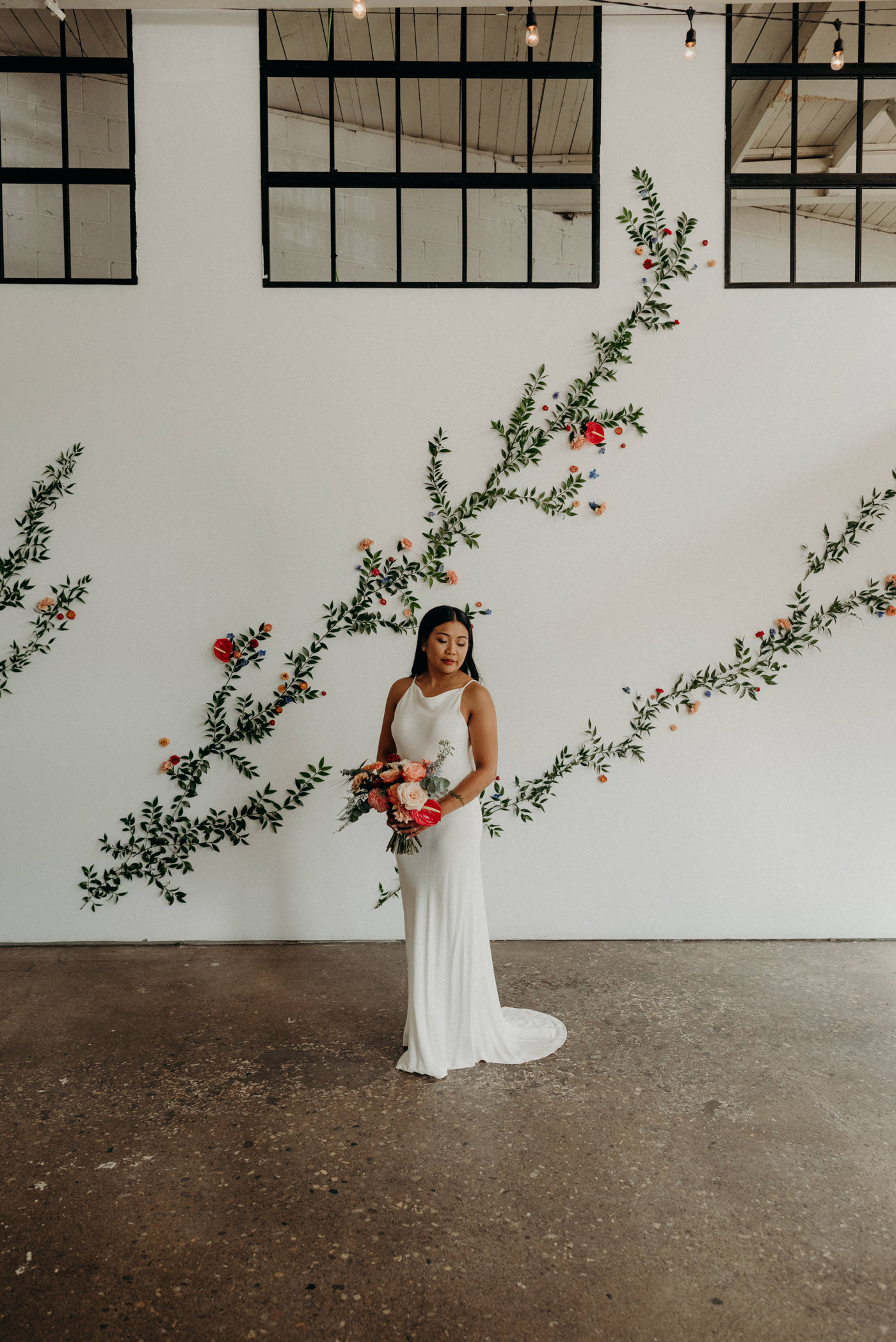 Bride standing in front of floral wall at Airship37