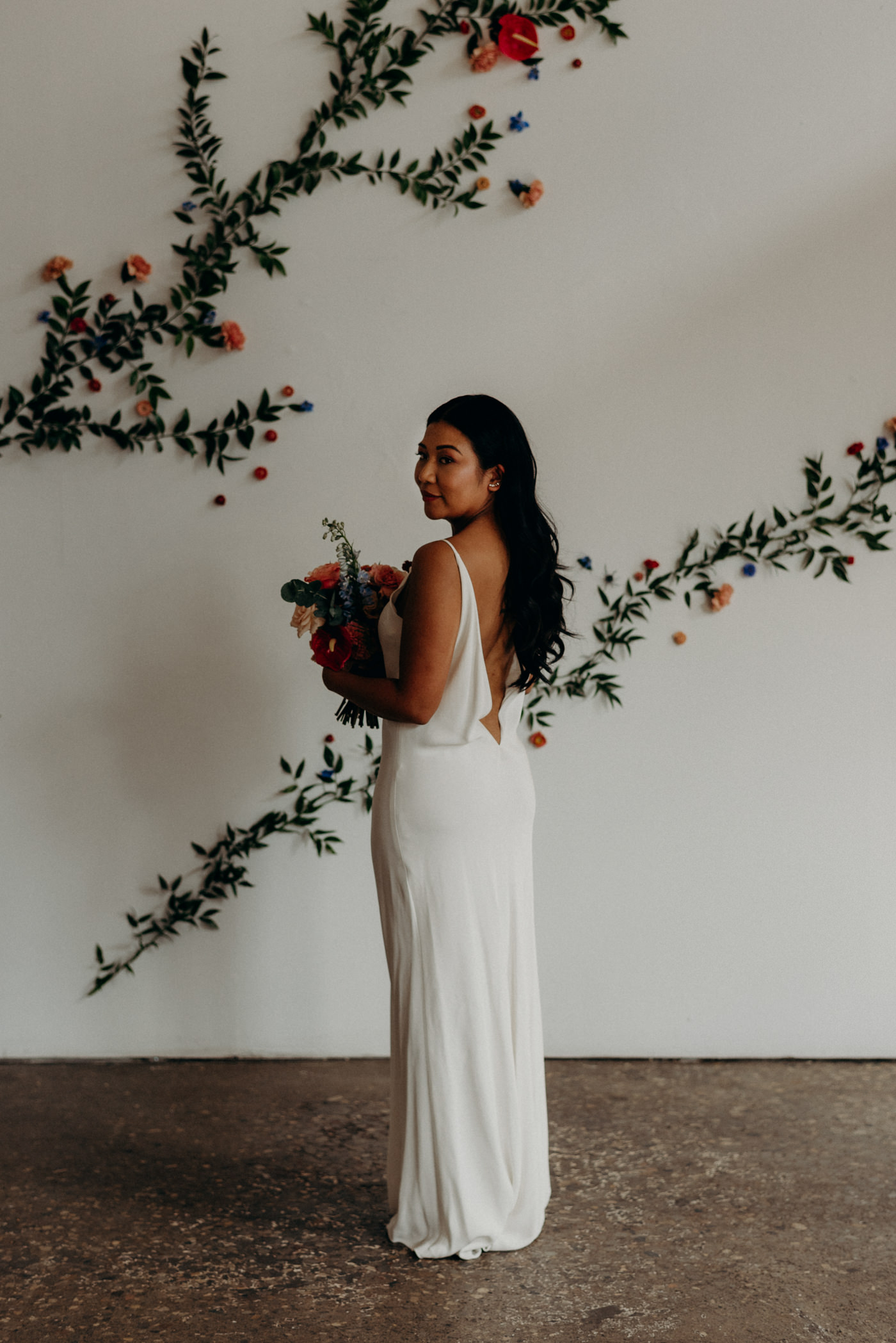 Bride in front of floral wall at Airship37 Wedding
