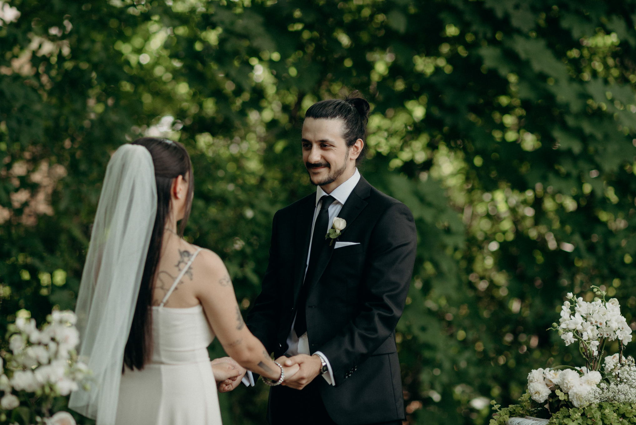 Groom smiling at bride during backyard wedding ceremony