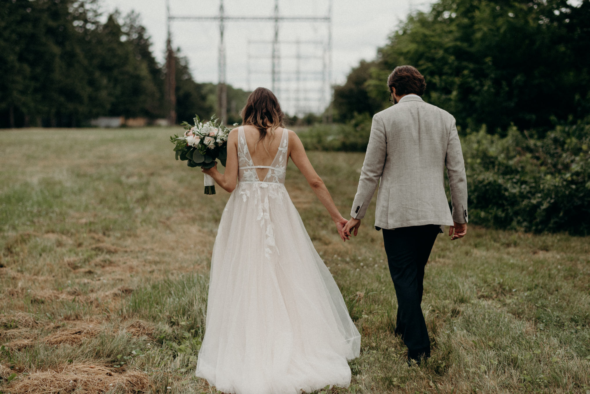 bride and groom walking holding hands in field