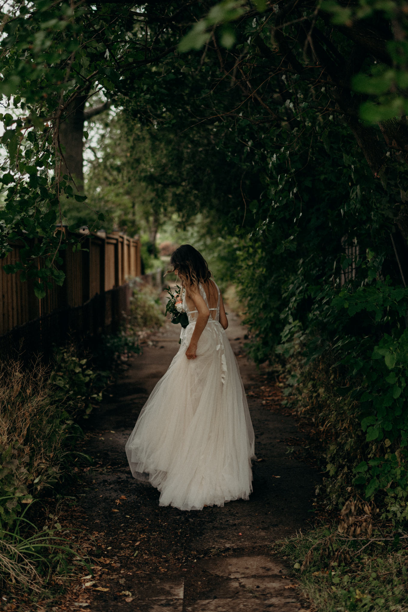 bride walking down alley near house