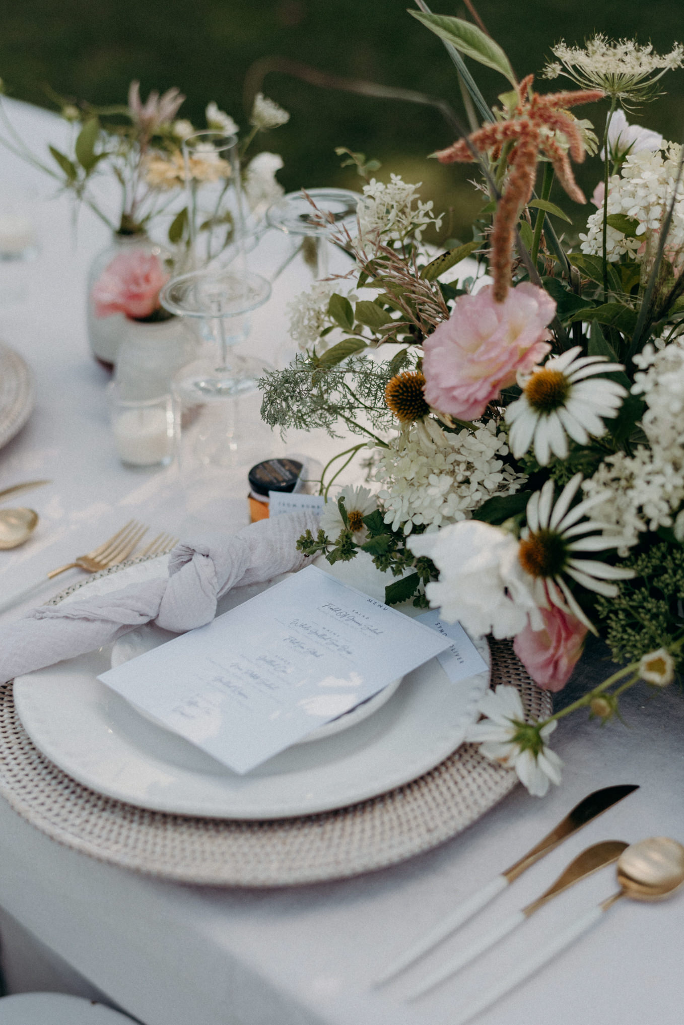 summery outdoor wedding reception table setting on white linens with white and pink flowers