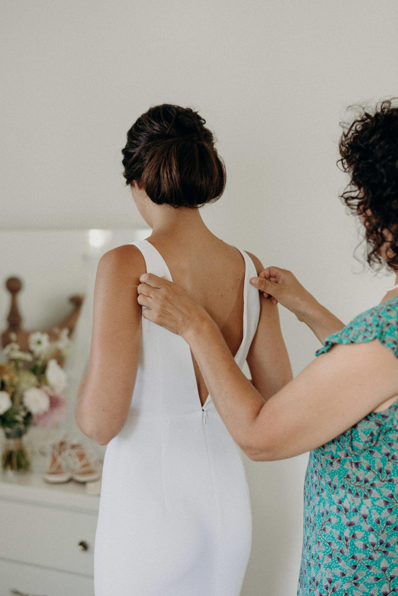 mother of bride helping adjust straps of dress