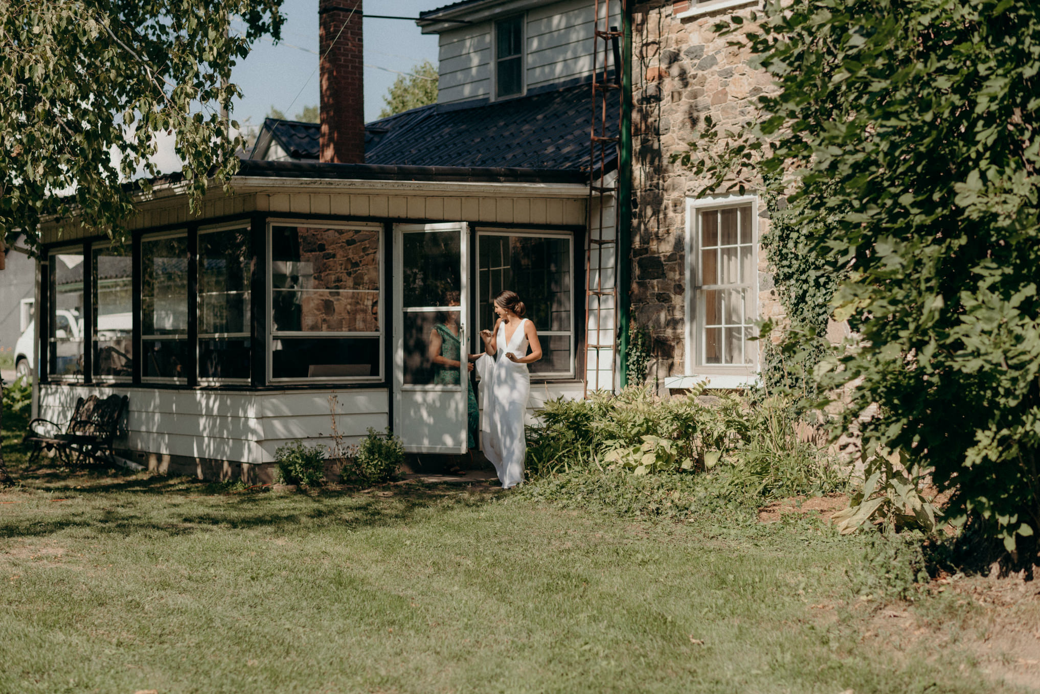 bride walking out of old farmhouse for first look