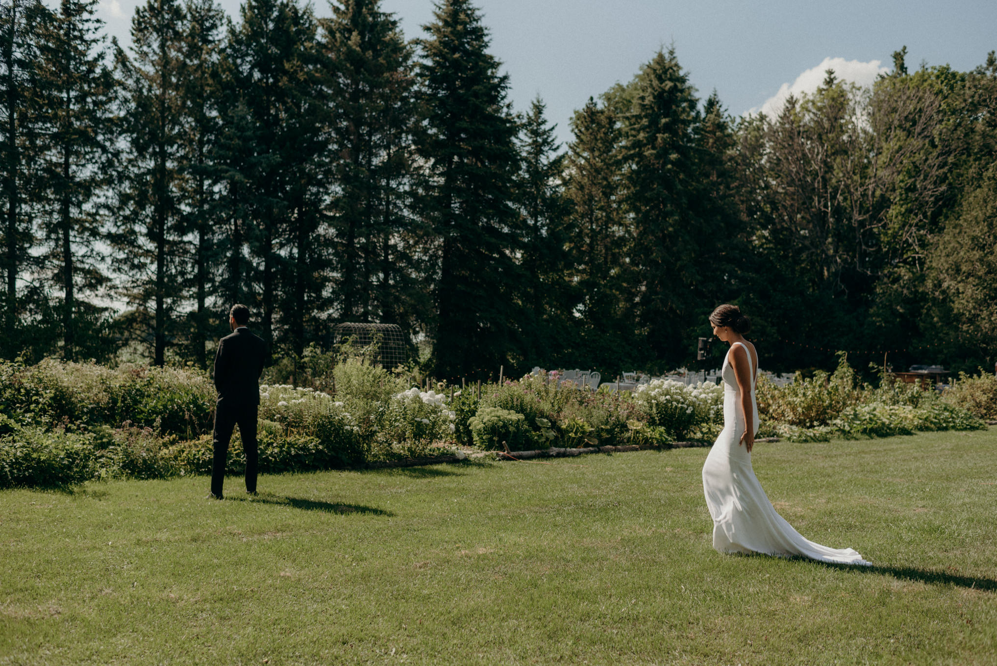 bride walking towards groom outside by garden for first look