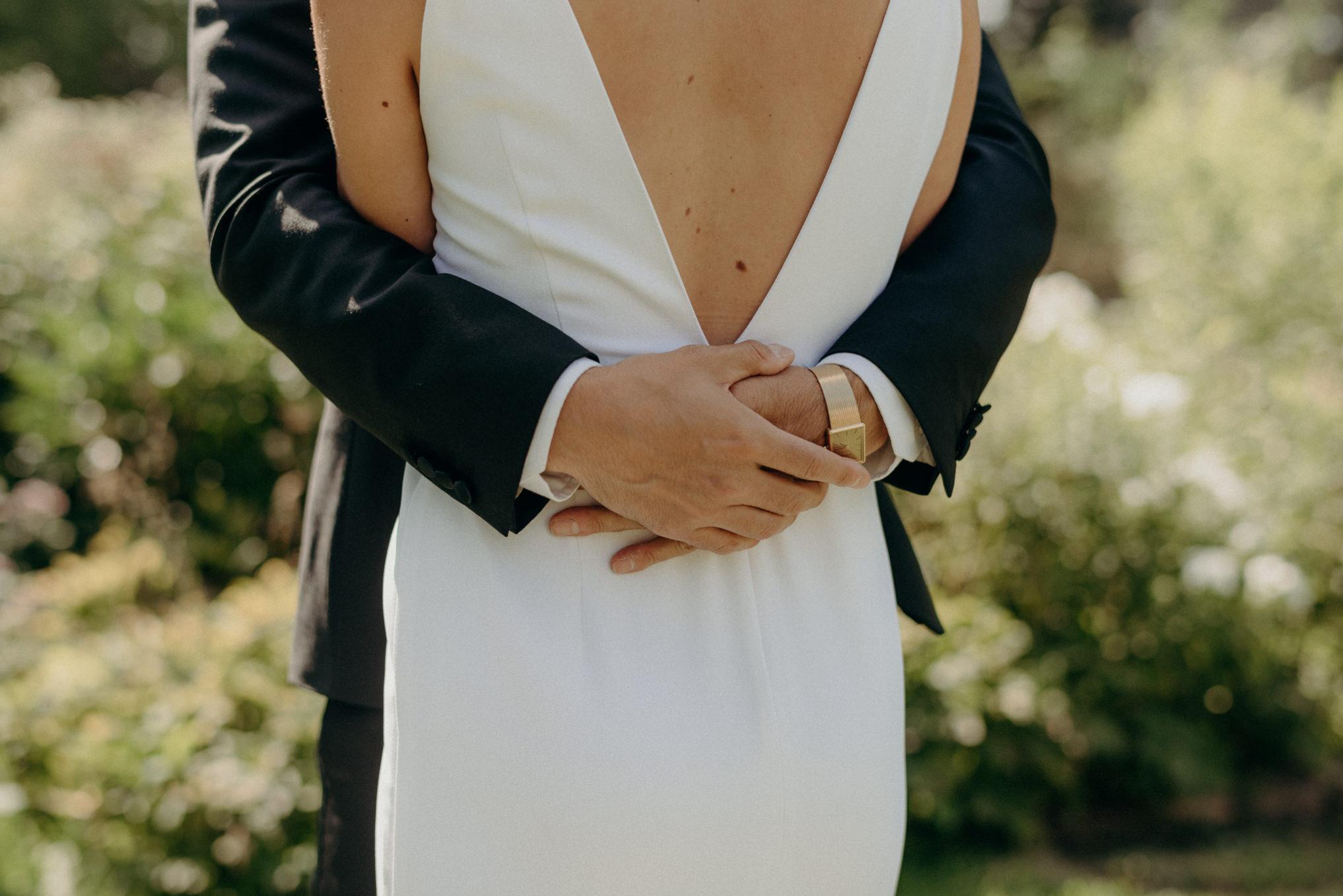 groom wearing vintage watch and hugging bride