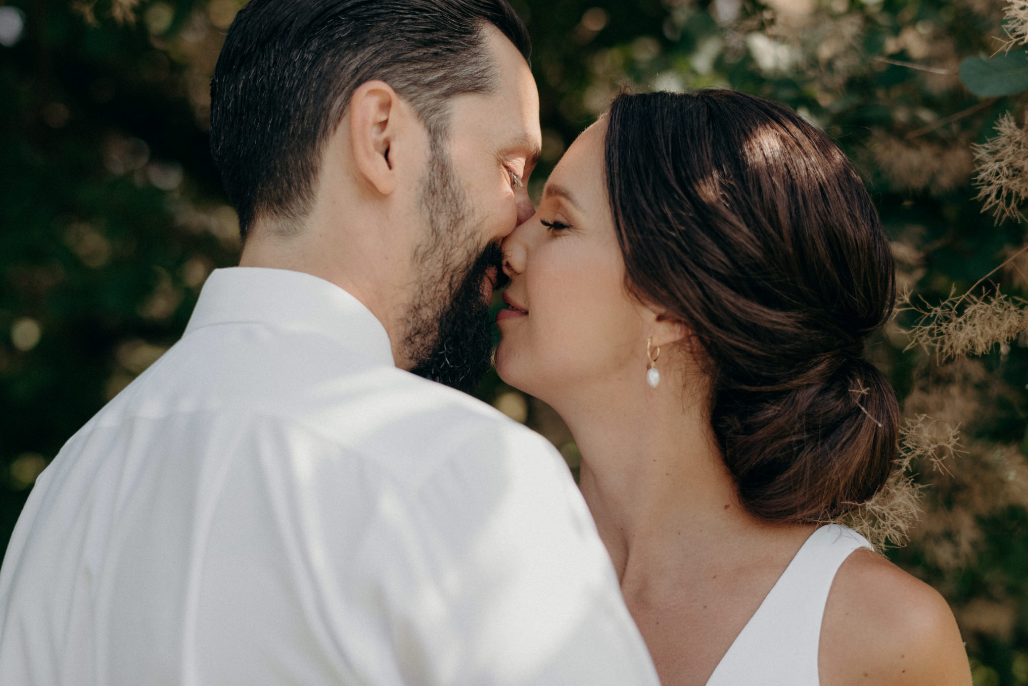 bride and groom about to kiss under smoke bush tree