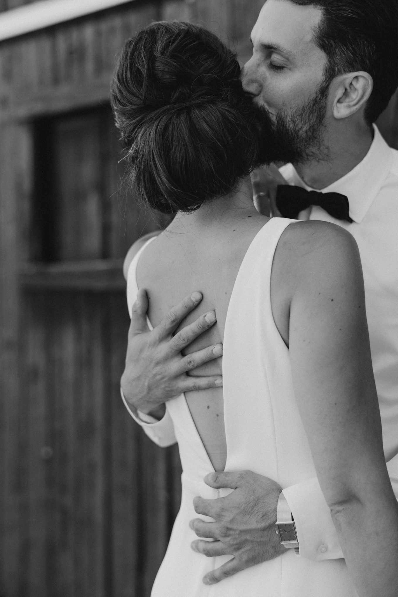 groom holding bride close as he kisses her head