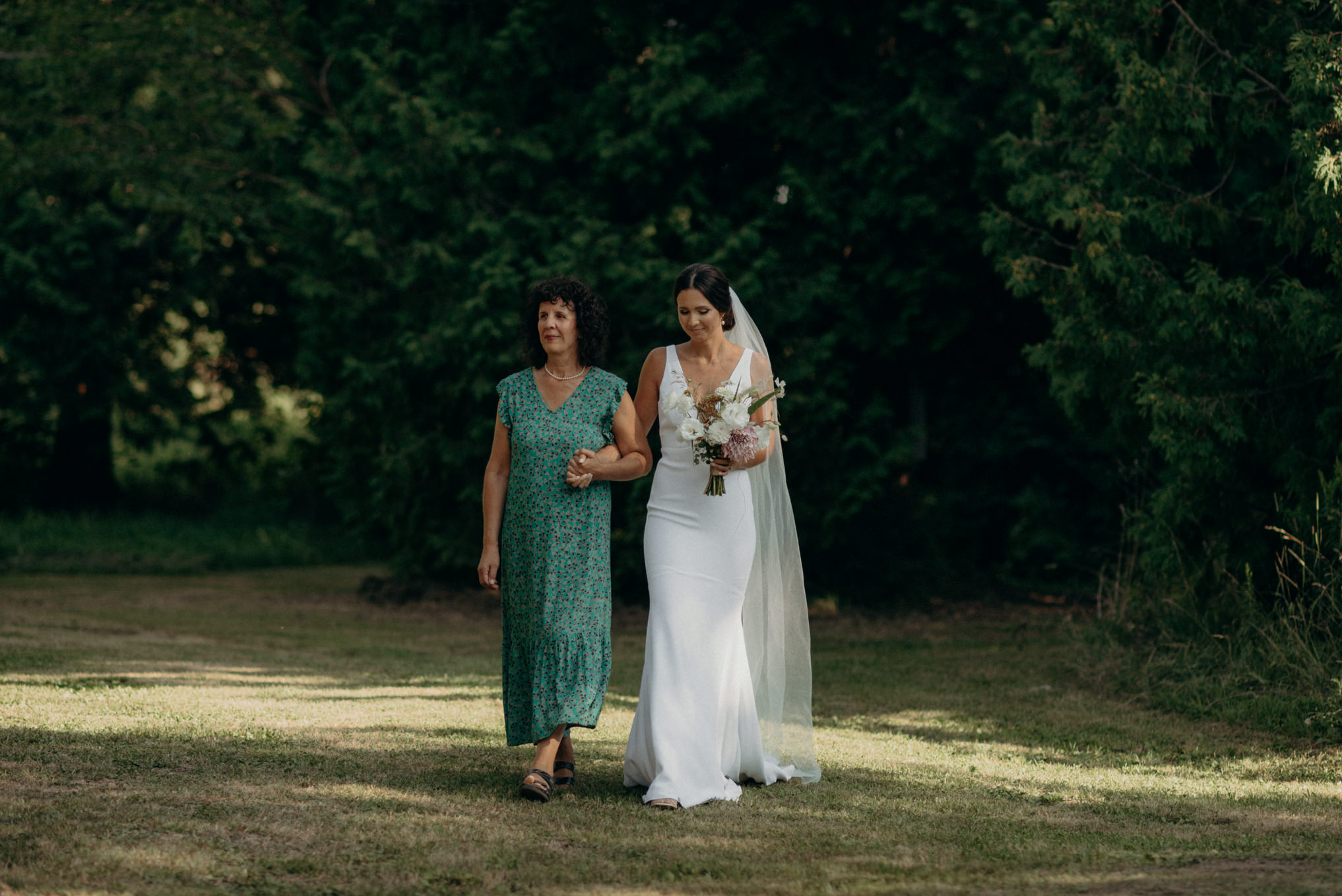 bride's mother walking her on lawn to ceremony