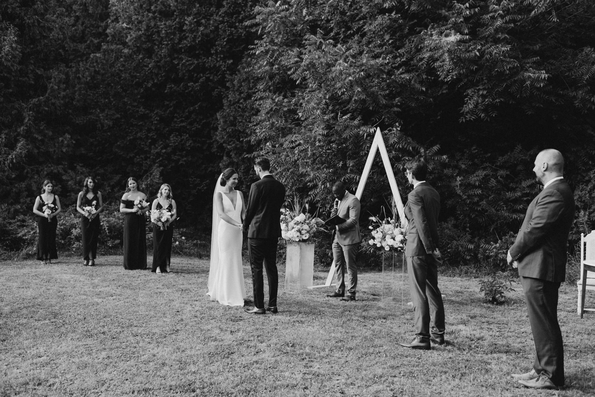 black and white of wedding ceremony outside surrounded by trees
