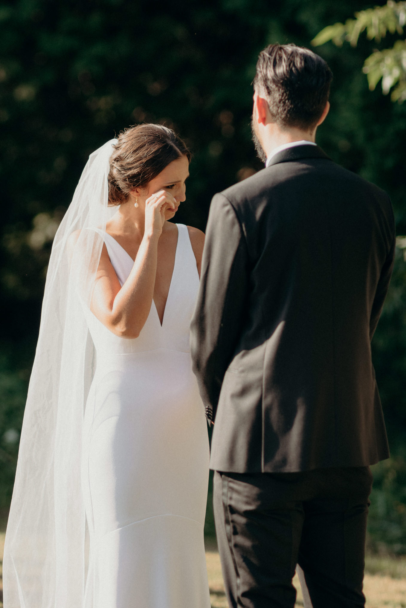 bride wiping away tear during wedding ceremony