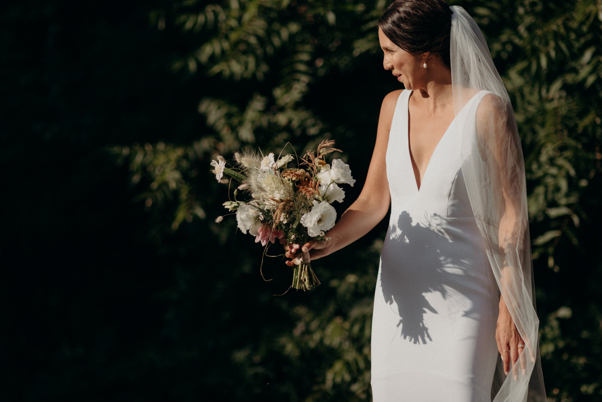 bride holding bouquet in sun surrounded by trees